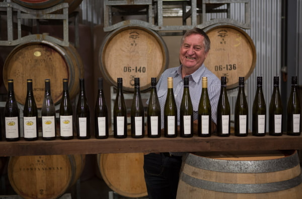 Man smilling at the camera with bottles of wine